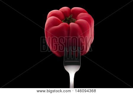 red bell pepper impaled on a silver fork on a black background