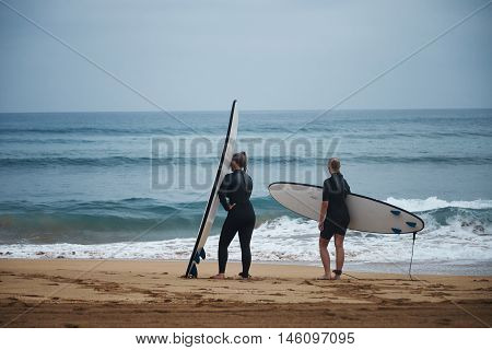 Two women in wetsuits with surfboards are getting ready to go into water on a cool summer day