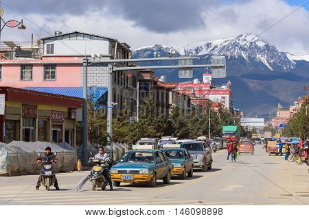 SHANGRI-LA, CHINA - April 20, 2016: Traffic intersection in the Shangri-la city with the snow mountains background.