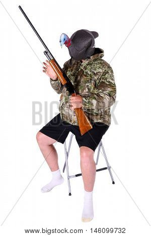 An Unidentifiable  Turkey Hunter dressed in Camouflage shorts and socks poses with his shotgun while wearing his Turkey Decoy on his head. isolated on white. room for text.