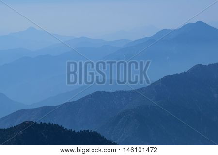 San Gabriel Mountains surrounded by haze which is a typical weather pattern in Southern California taken from Mt Baldy, CA