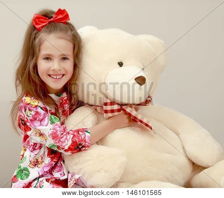 Happy little girl with a long ponytail down to his shoulders, and a red bow on her head, in a beautiful summer dress. Girl hugging a big Teddy bear. Close-up