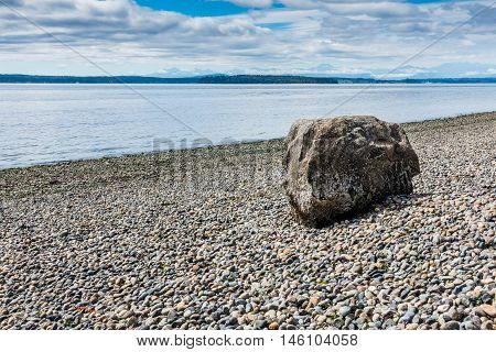 One rock sits on a bare shoreline at Lincoln Park in West Seattle Washington.