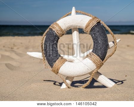 Life buoy placed on white starfish stuck on the sand beach against the sea