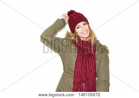 Portrait of modern young blonde Caucasian woman in olive green jacket, dark red knitted hat and scarf, posing, smiling, isolated on white background.