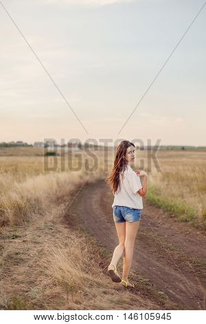Young girl with long brown hair walking away on the road in autumn field she turns around. Selective focus warm tinted.