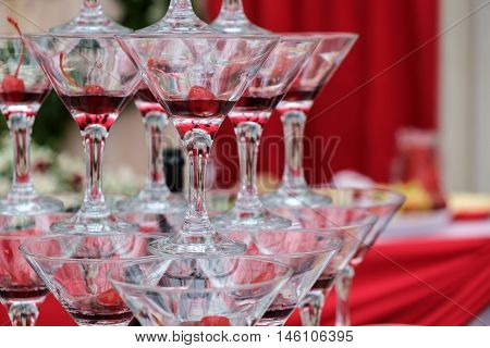 Champagne glasses stand on each other. Pyramid of champagne on the table. Holiday hill with glasses and cherries for wine at the Banquet.
