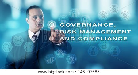 Mature business man with focused gaze is pushing a virtual button to activate GOVERNANCE RISK MANAGEMENT AND COMPLIANCE onscreen. Business concept for corporate governance laws and regulations.