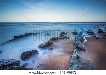 Long exposure of sea and rocks, sunrise shot