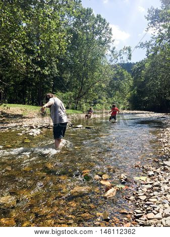 rocks and a babbling brook in the country with children playing