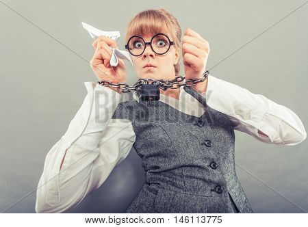 Business and stress concept. Terrified businesswoman in glasses with chained hands holding contract grunge background unusual angle view
