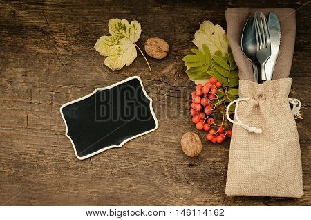 Thanksgiving autumn place setting with cutlery and arrangement of fall leaves and nuts on wooden background with chalkboard for text. Thanksgiving holidays background concept. Copy space. Top view.