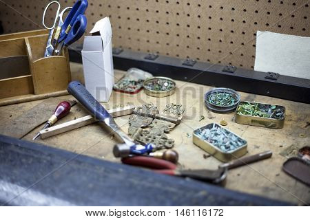 Various tools and tarnished copper buttons at a bookbinders workstation.