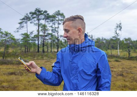 Young man checking up his smartphone outdoors in the gloomy northern landscape