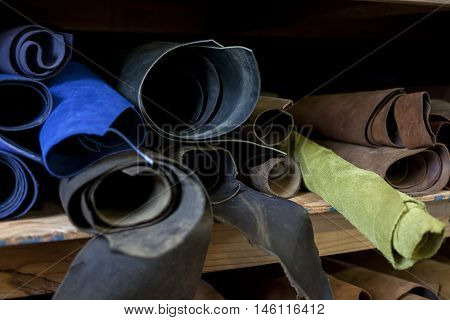Rolls of unused leather sit on a bookbinders shelf.