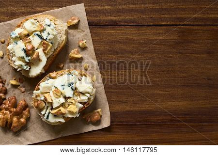 Blue cheese and walnut canapes photographed overhead on dark wood with natural light (Selective Focus Focus on the top of the canapes)