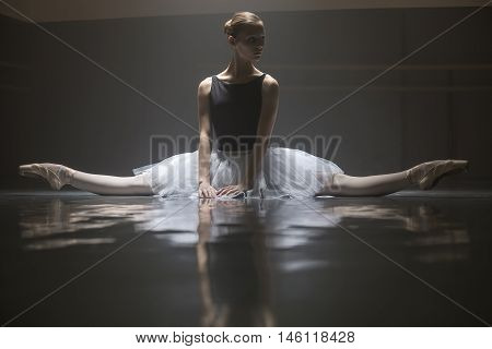 Cute ballerina in white tutu sitting on the splits in the dance hall. She puts her hands on the floor in front of her. Light falls down on her from above. She is reflected on the floor surface. Shoot in a low key.