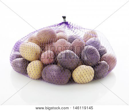 Raw Fingerling potatoes in a bag on white background
