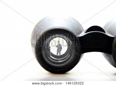 Business man figurine in the lens of binoculars