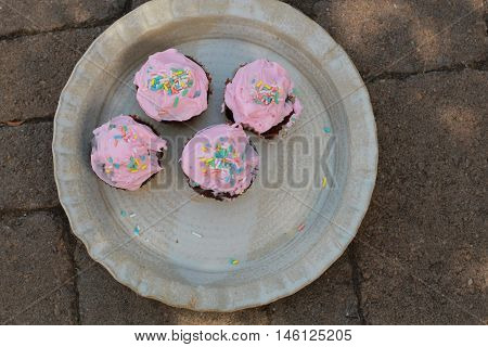 frosted pink cupcakes on a beige ceramic plate