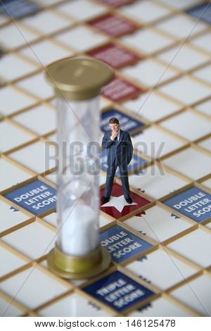Business man figurine standing on a scrabble game board looking at a sand timer.