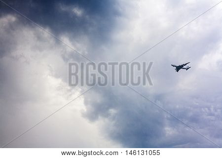 Passenger plane approaching against a stormy sky poster