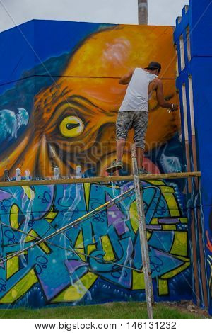 PUNTA DEL ESTE, URUGUAY - MAY 06, 2016: young man standing over a scaffold painting the final details of the grafitti.