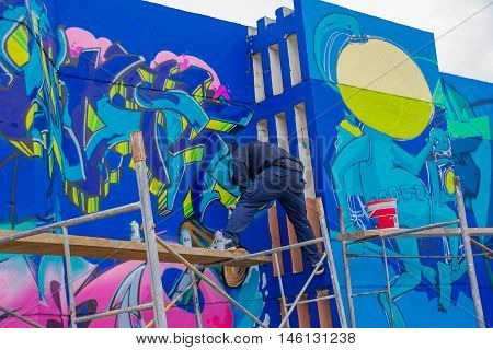 PUNTA DEL ESTE, URUGUAY - MAY 06, 2016: young man standing over a scaffold painting a grafitti.