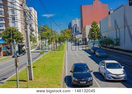 CURITIBA , BRAZIL - MAY 12, 2016: two cars waiting at the intersection, cable post located in the middle sidewalk.