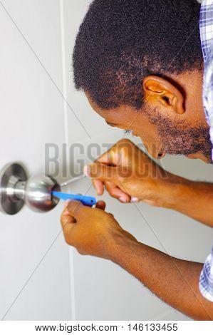 Closeup head and hands of locksmith using pick tools to open locked door.