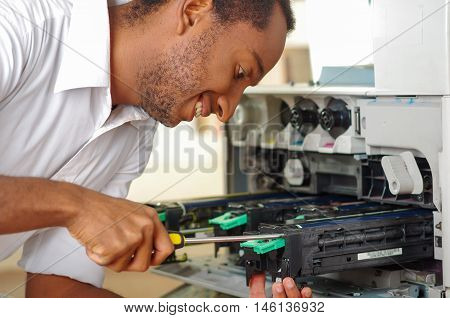 Man leaning over open photocopier during maintenance repairs using handheld tool, black mechanical parts.