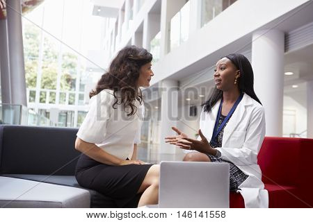 Doctor And Patient Having Meeting In Hospital Reception Area