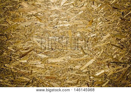 Oriented Strand Board. Building material. Wooden panel made of pressed sandy brown wood shavings as background closeup