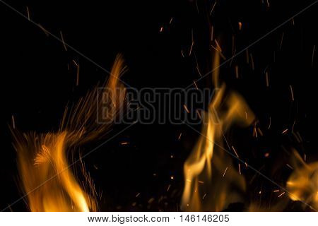 Burning fire with fiery orange flames sparks and embers exploding into the air on a dark background with copy space