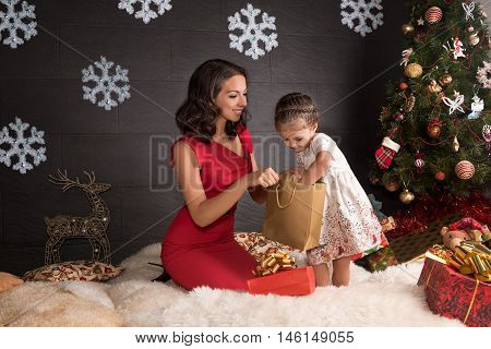 Happy mother with small daughters open a Christmas gift