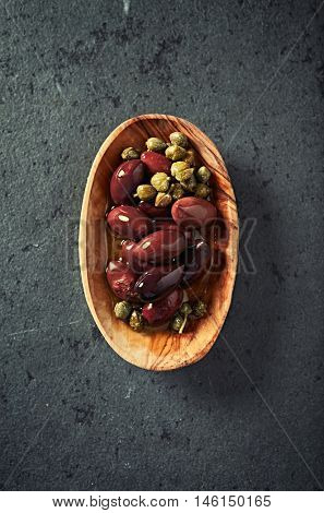 Kalamata olives and capers in a wooden dish