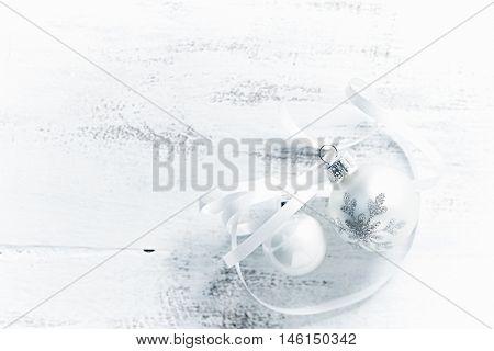 White Christmas balls on a white wooden background