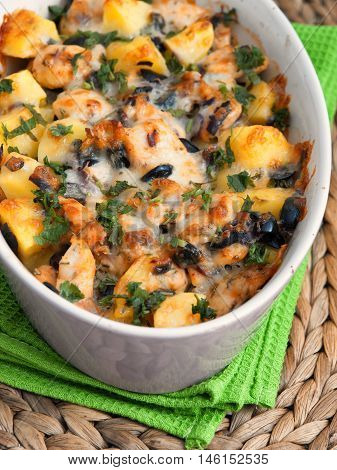 Casserole dish with potatoes chicken breasts olives and fresh herbs. Vertical shot
