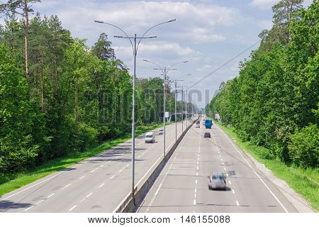 View from above of the motorway with asphalt surface lampposts traffic barriers and forest on both sides in summer day