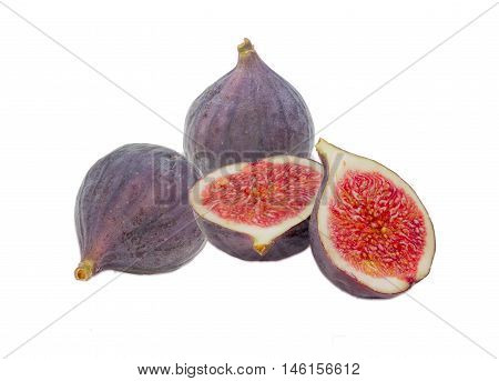 Two whole fresh ripe fig fruit and one fig cut in half on a light background