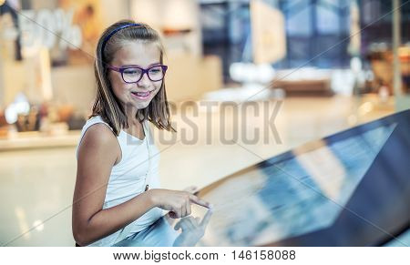 Beautiful cute little girl studying orientation plan in shopping mall. Shopping Center Store Guide. Modern touch screen technology. Toned image.