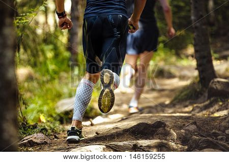 male marathon runner running woods on feet compression socks. a dynamic and explosive running. closeup of trainers