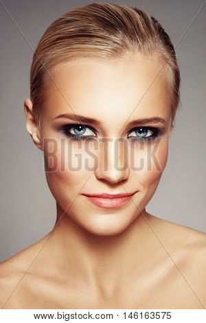 Portrait of young beautiful tanned woman with freckles and smoky eye make-up