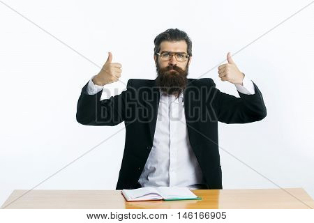 young handsome bearded man scientist or professor with long beard and teacher glasses with book or notepaper sitting at table with thumbs up isolated on white background