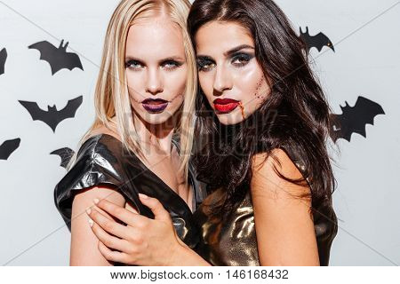 Two beautiful young women with halloween makeup standing over white background