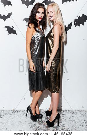 Full length of two attractive young women with vampire makeup standing and posing over white background