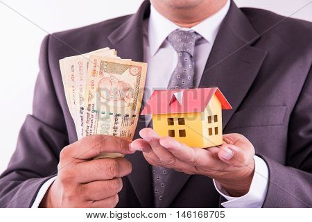 buying home concept, indian man holding indian currency notes in one hand and small model house in second hand, closeup and selective focus