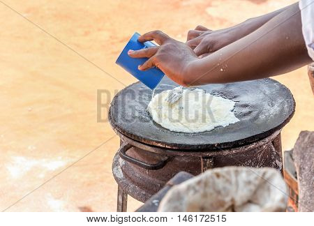 Preparation of traditional Ugandan breakfast Rolex made with chapati and eggs