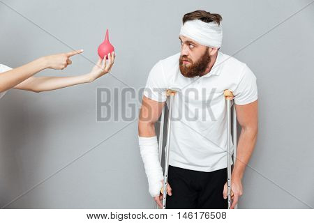 Scared panicked bandaged injured man going to have an enema procedure over gray background