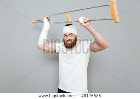 Mad aggressive young man rased and going to fight with crutches over white background